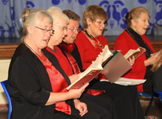 Close up of five choir members singing during a  rehearsal.